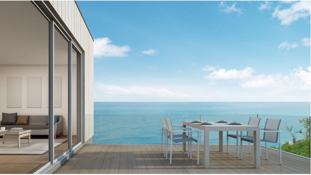 Large glass and aluminium bi-fold doors like those SHEAR Glass and Aluminium can supply and install across Sydney. Opening out on to beautiful view of the sea with decking and outdoor dining area